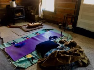 A stage set for self pleasuring that includes yoga mat, meditatin cushion, lingerie, vibrator, lubrication